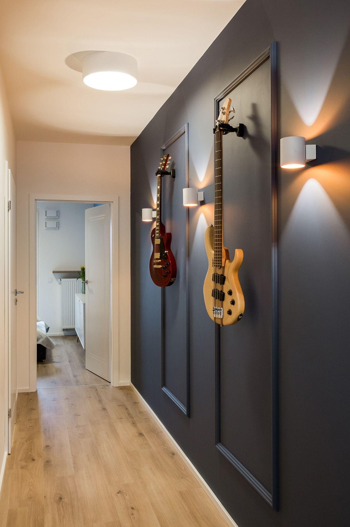 Către dormitoare peretele a fost tratat decorativ, cu baghete de polisitiren vopsite în aceeași nuanță, care să formeze rame discrete pentru două chitări. Iluminatul cu aplice este și funcțional, dar și decorativ.