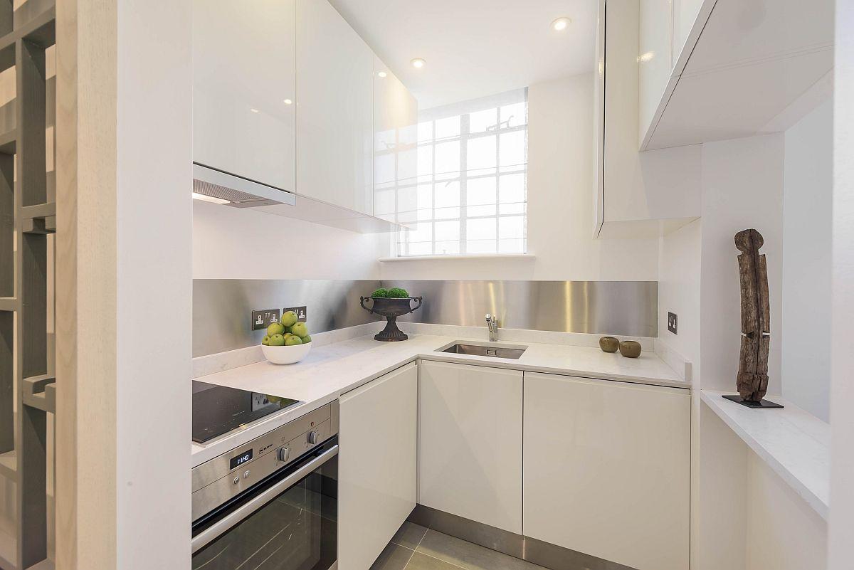 Bucătăria este mică, dar excelent organizată printr-o mobilare gândită la milimetru. S-a lăsat spațiu de depozitare generos între plită și chiuvetă, iar frigiderul este încorporat. Da, compromisul făcut a fost în privința combinei frigorifice, dar designerii au avut în vedere suplimentarea spațiului de depozitare prin corpurile suspendate, cele inferioare fiind ocupate de către electrocasnice mari încorporate.