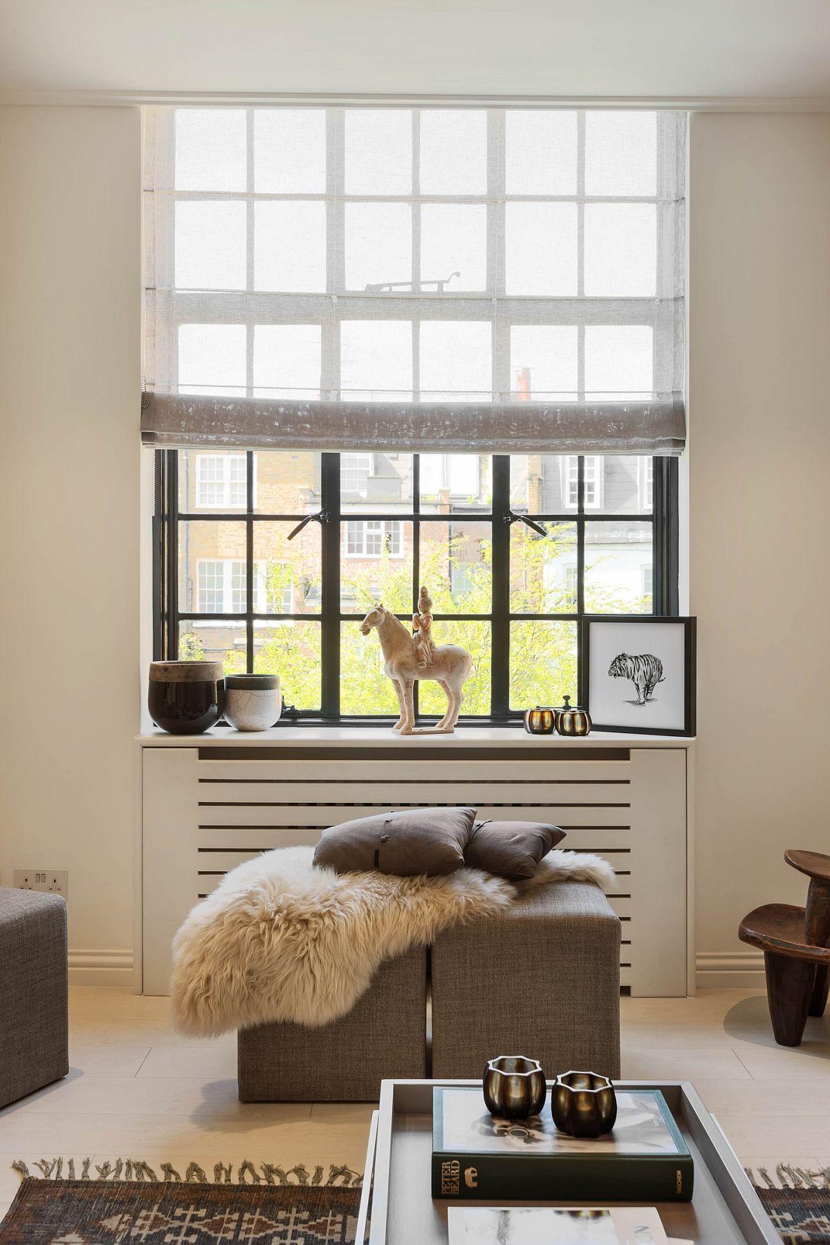 Singura fereastră din camera garsonierei este decorată astfel încât să pătrundă cât mai multă lumină naturală, iar suprafața geamului să fie în mare parte la vedere (prin instalarea unui stor). Masca de calorifer ascunde un element tehnic, dar devine și piesă de mobilier - loc de expunere a obiectelor decorative. În fața ferestre două taburete sunt piese versatile ce pot fi folosite în zona de conversație, dar și sprijin pentru picioare cînd se stă pe canapea. Ele nu ocupă mult spațiu în cameră, dar sunt utile.
