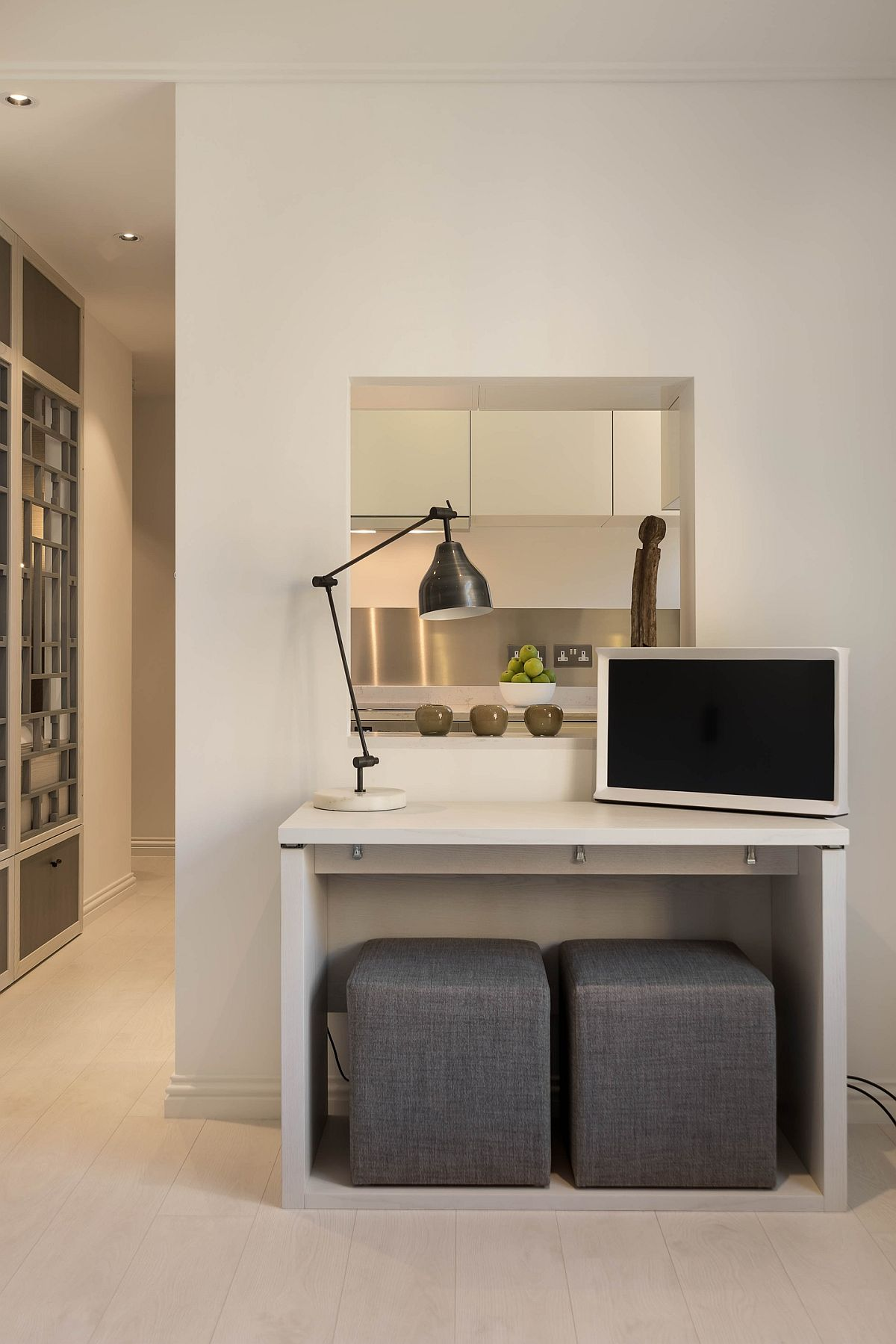 Locul de birou este și loc de tv, dar piesa de mobilier este versatilă putînd fi extinsă ca și masă în cameră. Un mic oficiu către bucătărie alungă senzația de spațiu mic. Taburetele pot deveni locurile de ședere la masa de birou ce poate fi extinsă ca masă de sufragerie.