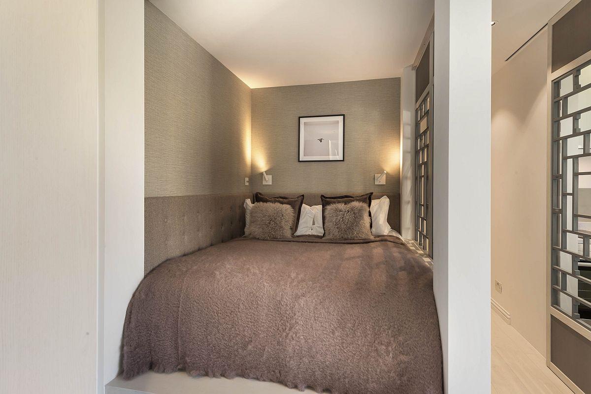 Pentru mai mult confort toată, pereții din zona patului sunt îmbrăcați cu tapt, iar tăblia patului este prevăzută și în lateral. Nuanțele mai închise folosite aici dau senzația de adîncime dinspre living. Totul ambientat în tonuri similare pentru cât mai puține fragmentări vizuale, ceea ce conferă un aer unitar, liniștitor.