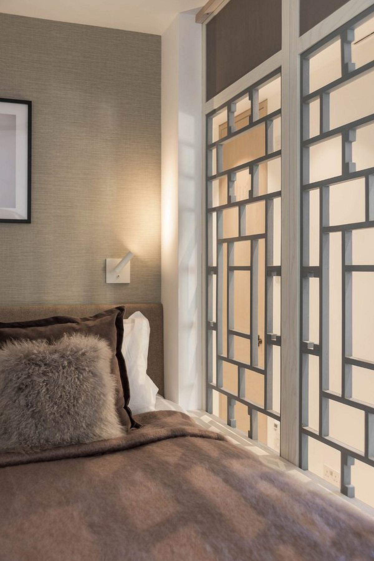 Panourile decorative ce separă patul, folosite și pentur ușa culisantă de la bucătărie, sunt inspirate din desenul ferestrei din living. Realizate pe comandă, ele maschează, dar și decorează în același timp. Prezența aplicelor de perete a fost gândită din faza de proiect, așa că și iluminatul puctat este rezolvat.