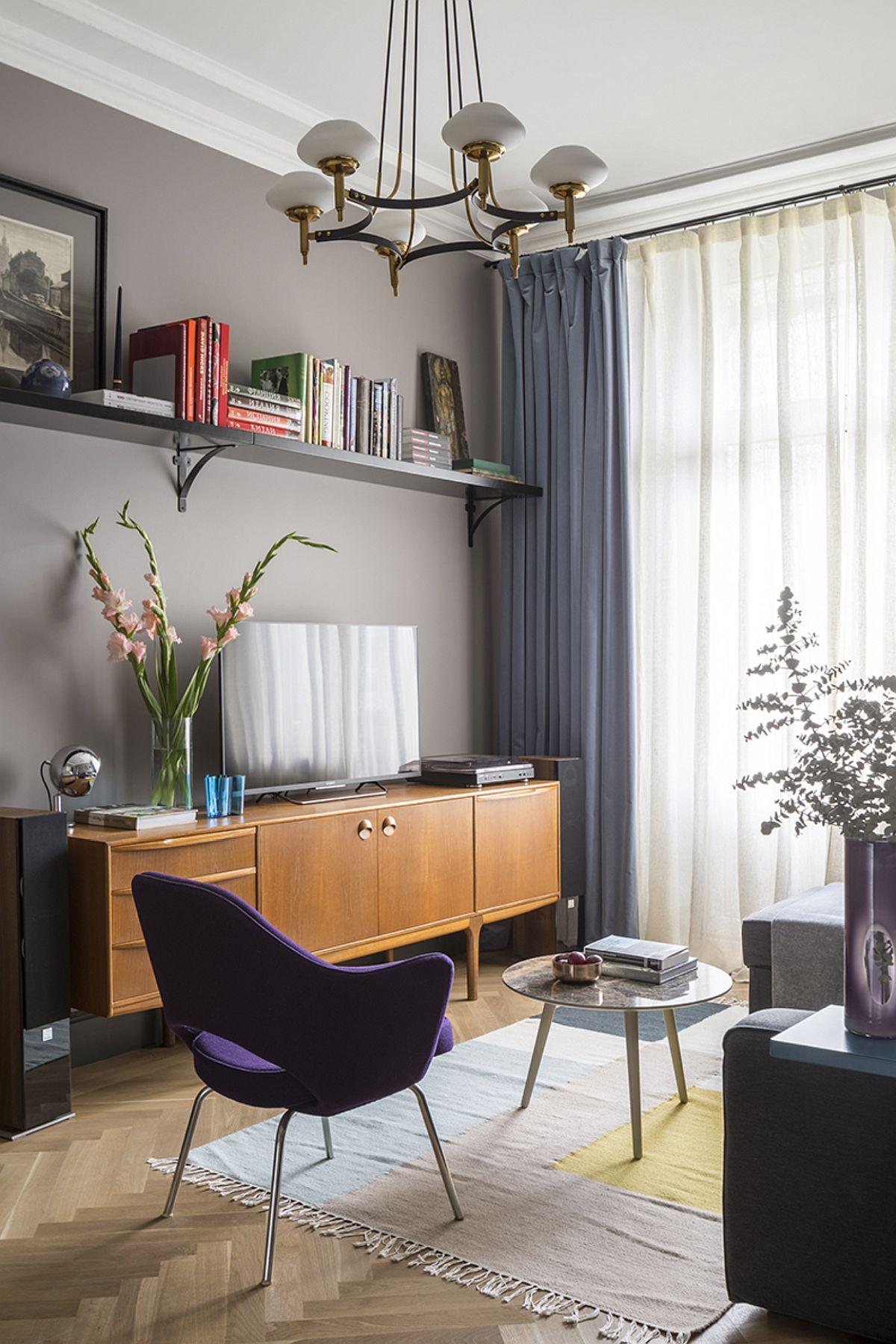Mobila din camera de zi este minimală, dar cu piese de design vintage. În locul unui ansamblu obișnuit pentru living, un raft superior oferă loc de depozitare și expunere obiecte, dare și ordonează camera. Apoi o comodă joasă servește și ca loc de tv, dar și pentru depozitare.