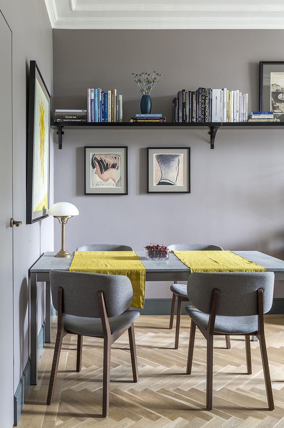 Accesul în camera de zi coincide cu cel în sufragerie. Pentru a economisi spațiu, designerul a prevăzut așezarea unei mese lipită cu latura îngustă de perete care separă dressingul. În stânga se poate observa ușa dressingului configurată în același plan cu zidul, astfel încât să nu fragmenteze spațiul.