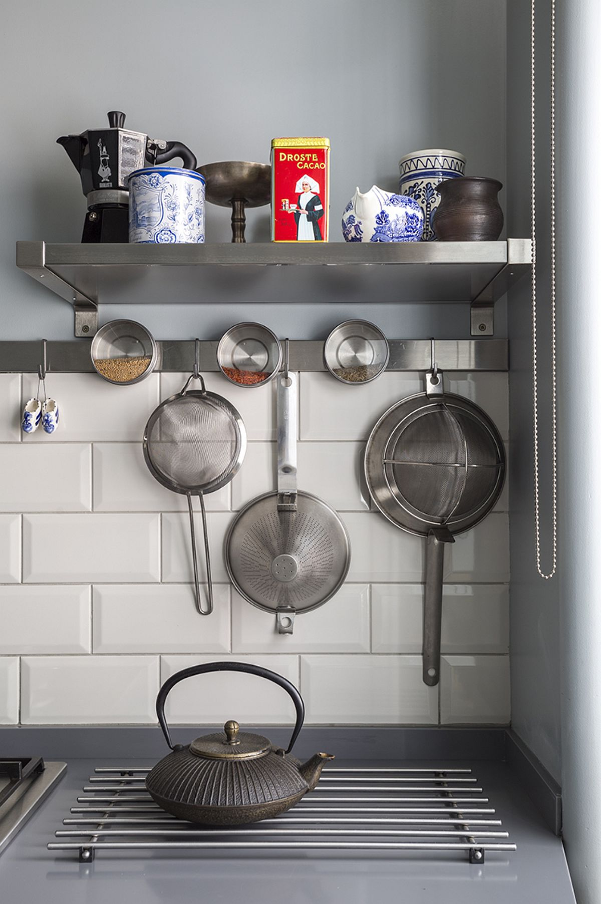 Orice spațiu pe verticală merită exploatat într-un spațiu mic, cum este și cazul acestei bucătării. Și da, chiar dacă este mică, pereții nu sunt îmbrăcați până sus cu faianță, ci doar în zona sensibilă. Pentru cei care vor curățenie maximă în bucătărie accesoriile din inox sunt o variantă bună.