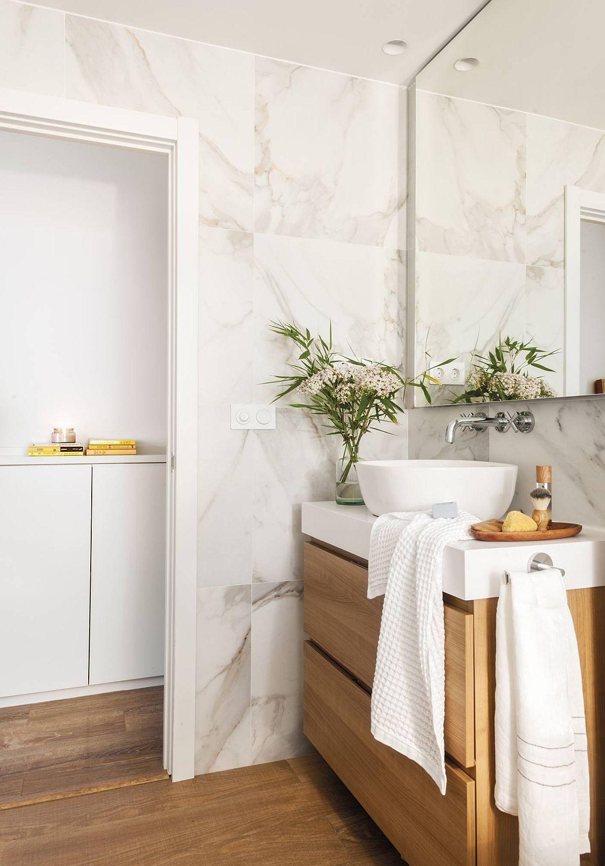 Camera de baie este finisată cu o gresie aleasă asortat cu parchetul din cameră, astfel că pardoseala pare că se continnuă. Pereți sunt placați cu plăci care imită desenul marmurei, iar oglinda supradimensionată dă impresia de spațiu mai amplu și luminos.