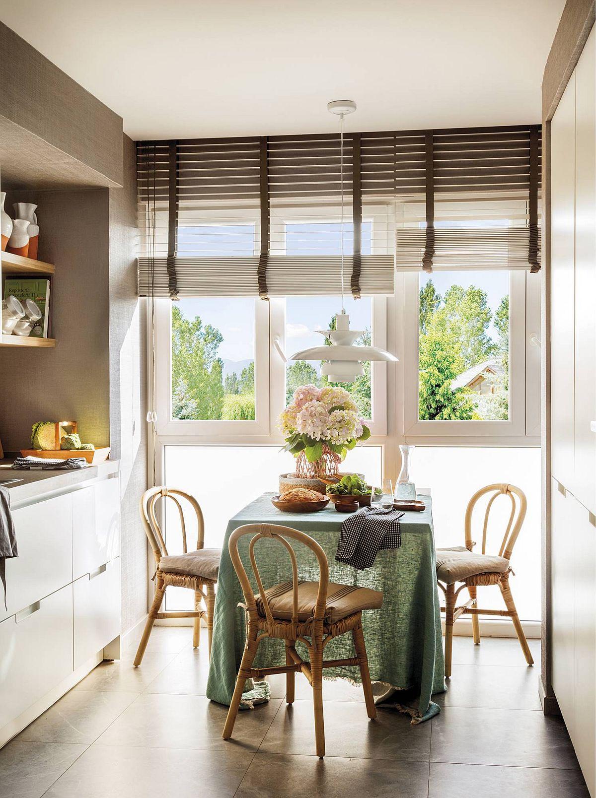 Pentru locul de luat masa s-a căștigat spațiu important, deși nu ai crede că doar 60 de centimetri pot face diferența dintre o bucătărie simplă și una cu loc pentru masă. Modul de ambientare contează și el în felul în care se simte bucătăria (mobilier de grădină pentru zona de masă), dar și faptul că fereastra este generoasă, practic până jos, partea inferioară fiind cu sticlă mată.