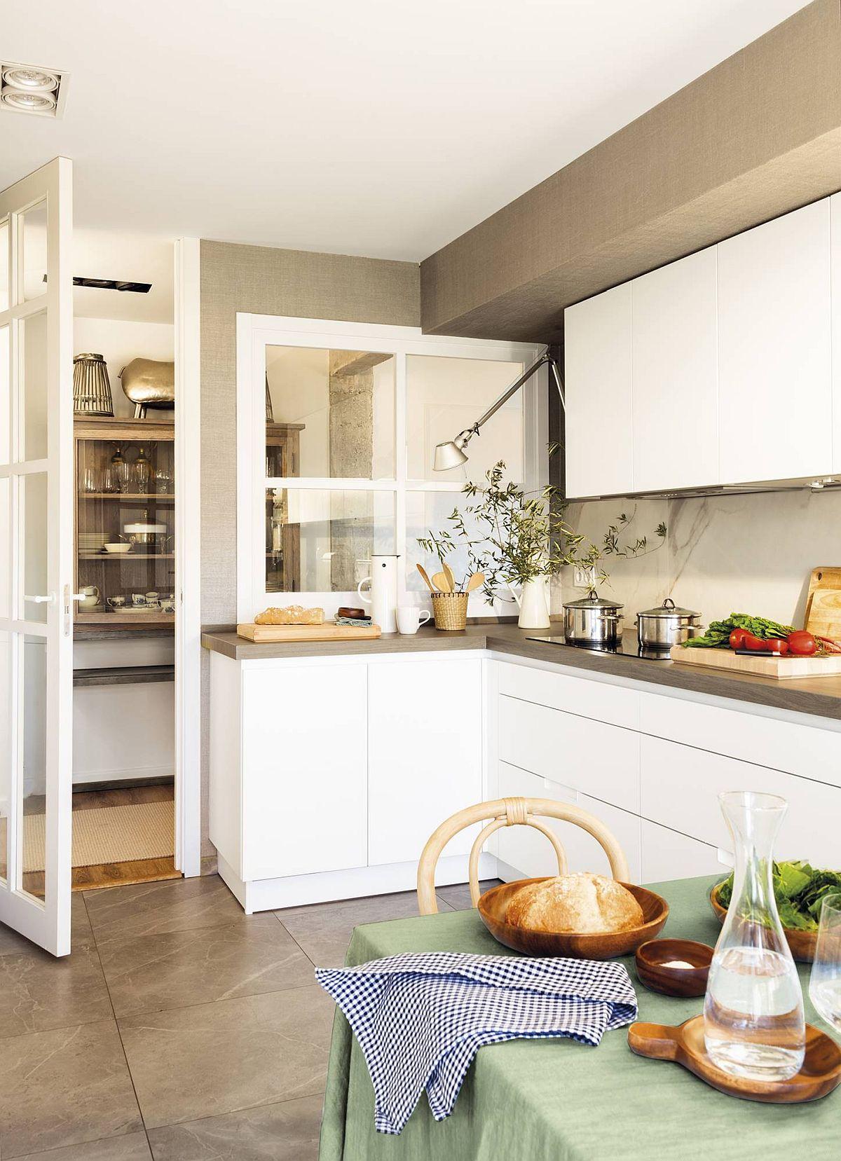 Deschiderea bucătăriei către hol dă impresia de spațiu mai mare în bucătărie. Separarea s-a făcut cu tîmplărie din lemn cu geamuri.