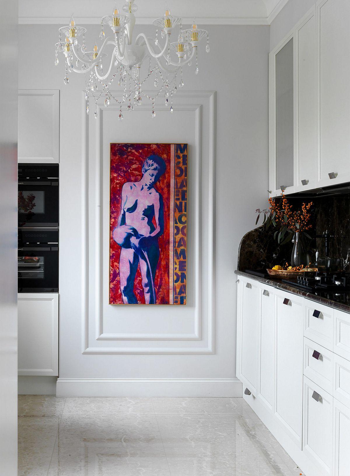 Din zona locului de luat masa se vede bucătăria, tratată la fel de artistic. Pentru a anihila caracterul ei tehnic, designul a prevăzut ca pe peretele ce se vede direct din zona de zi să fie amplasat un tablou. În rest amenajarea este cu aer clasic, mobila fiind o combinație de alb și negru. Zona de blat este tratată închis pentru ca electrocasnicele să fie mai bine camuflate.