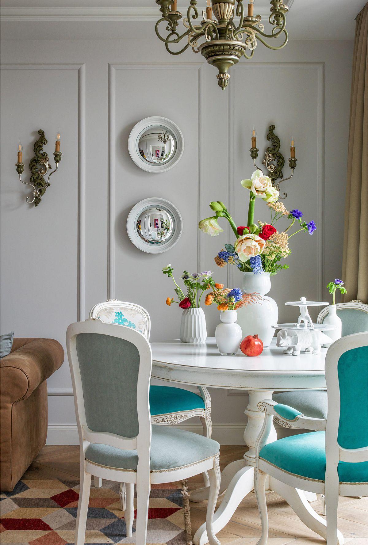 Locul de luat masa este strategic amplasat lângă fereastră, iar mobila aleasă este una cu alură clasică o combinație de alb și verde turcoaz care captează privirea.