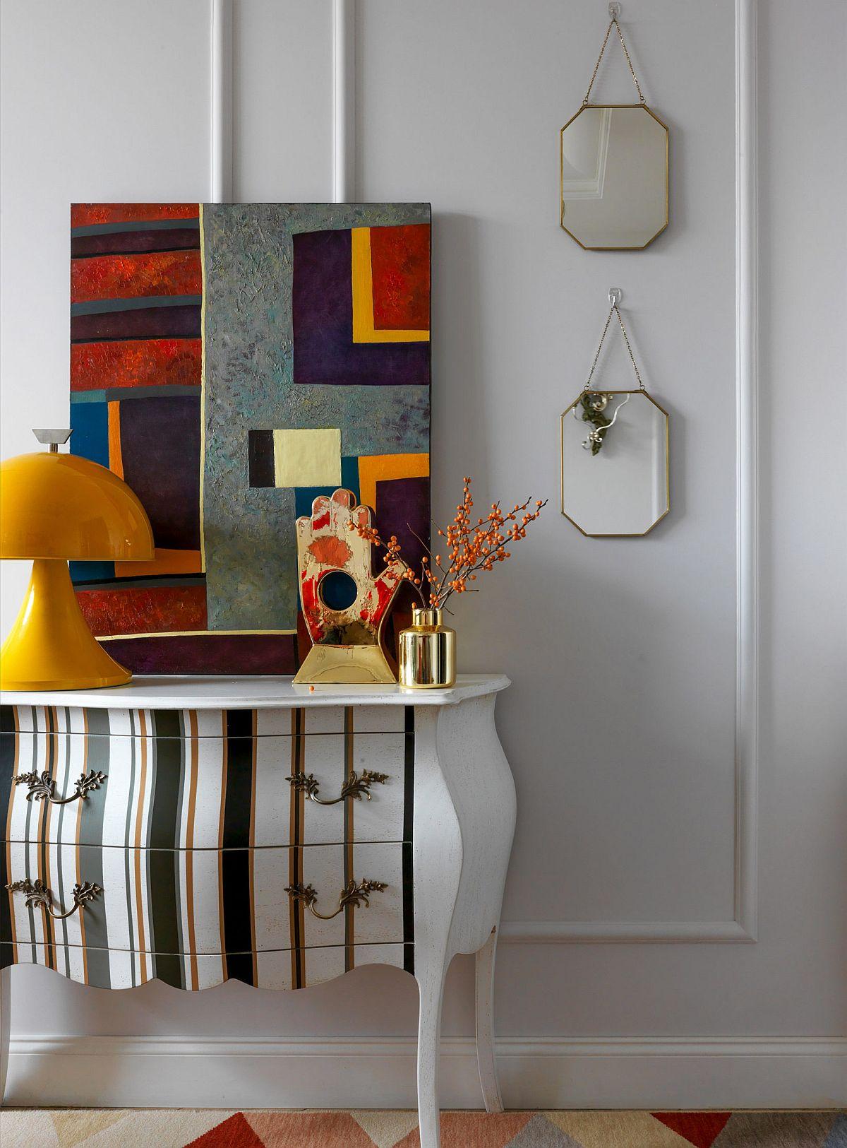 În fața canapelei o comodă clasică, dar actual personalizată este suportul perfect pentru lucrări de artă contemporană care personalizează prin mesaj, formă și culoare.