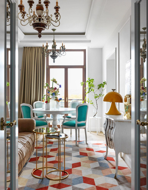 Separarea livingului față de holul de intrare s-a făcut cu o ușă dublă cu sticlă, care lasă lumina naturală să pătrundă către hol. Dar ambientul colorat care se vede odată ce intri în casă îți dă o stare de bine. Un contrast de verde turcoaz și petele de roșu de la nivelul covorului conferă vivacitate ambientului, iar candelabrele sunt neașteptate aici la fel ca și piesele de mobilier decorate și lucrările de artă.