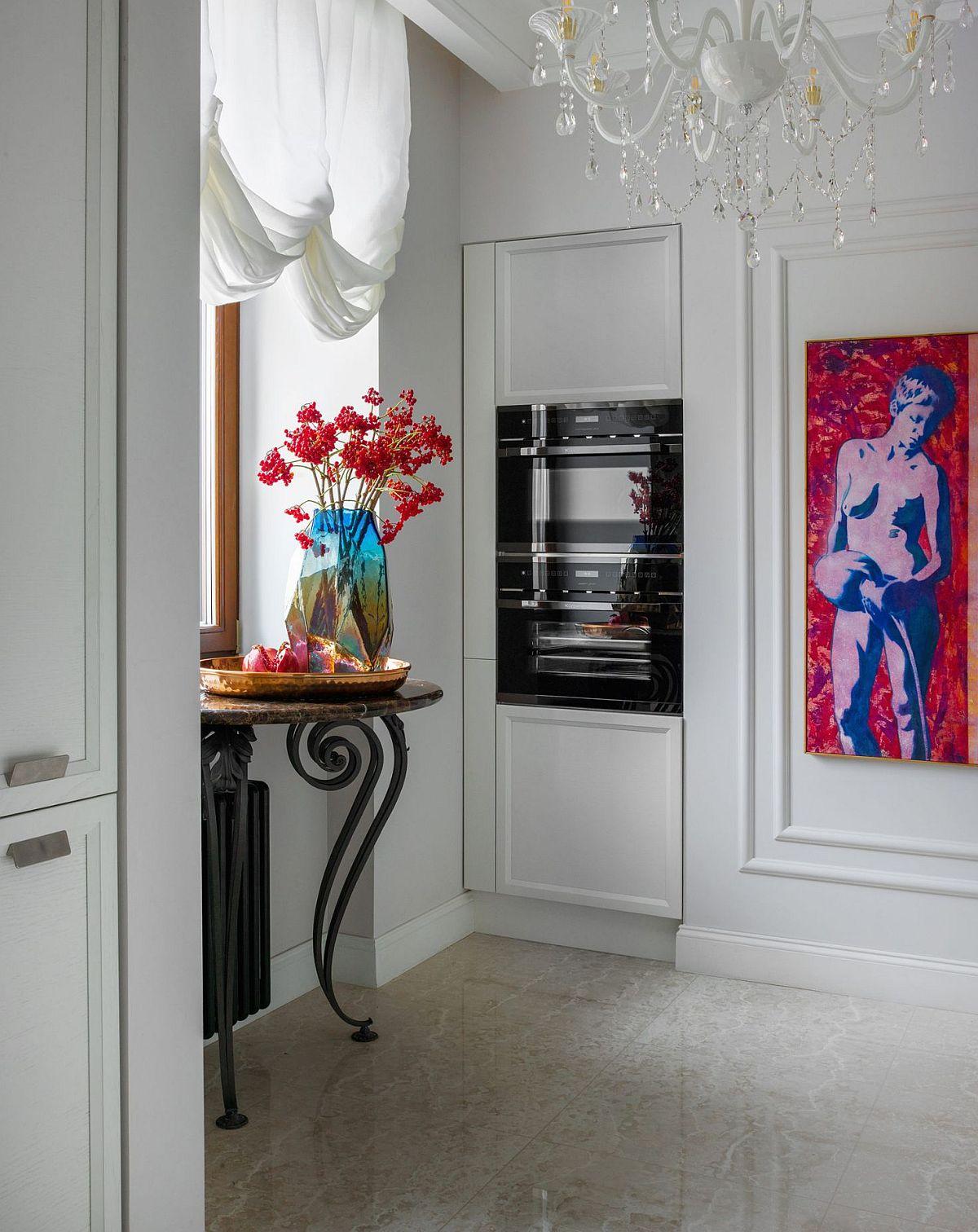 Spațiul bucătăriei este mic, dar designerul a prevăzut aici o masă consolă care poate fi folosită la nevoie ca loc pentru mic dejun. Combina frigorifică este încorporată într-un corp aflat în imediata apropiere a sufrageriei pentru a putea fi accesată mai rapid.