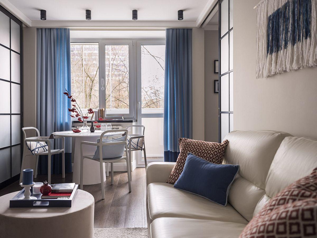 Panourile culisante care separă bucătăria și dormitorul față de camera de zi sunt gândite simetrice, astfel că imaginea livinguui este una armonioasă. Ba mai mult, ușile culisante au permis instalarea unui loc de luat masa în fața ferestrelor balconului.