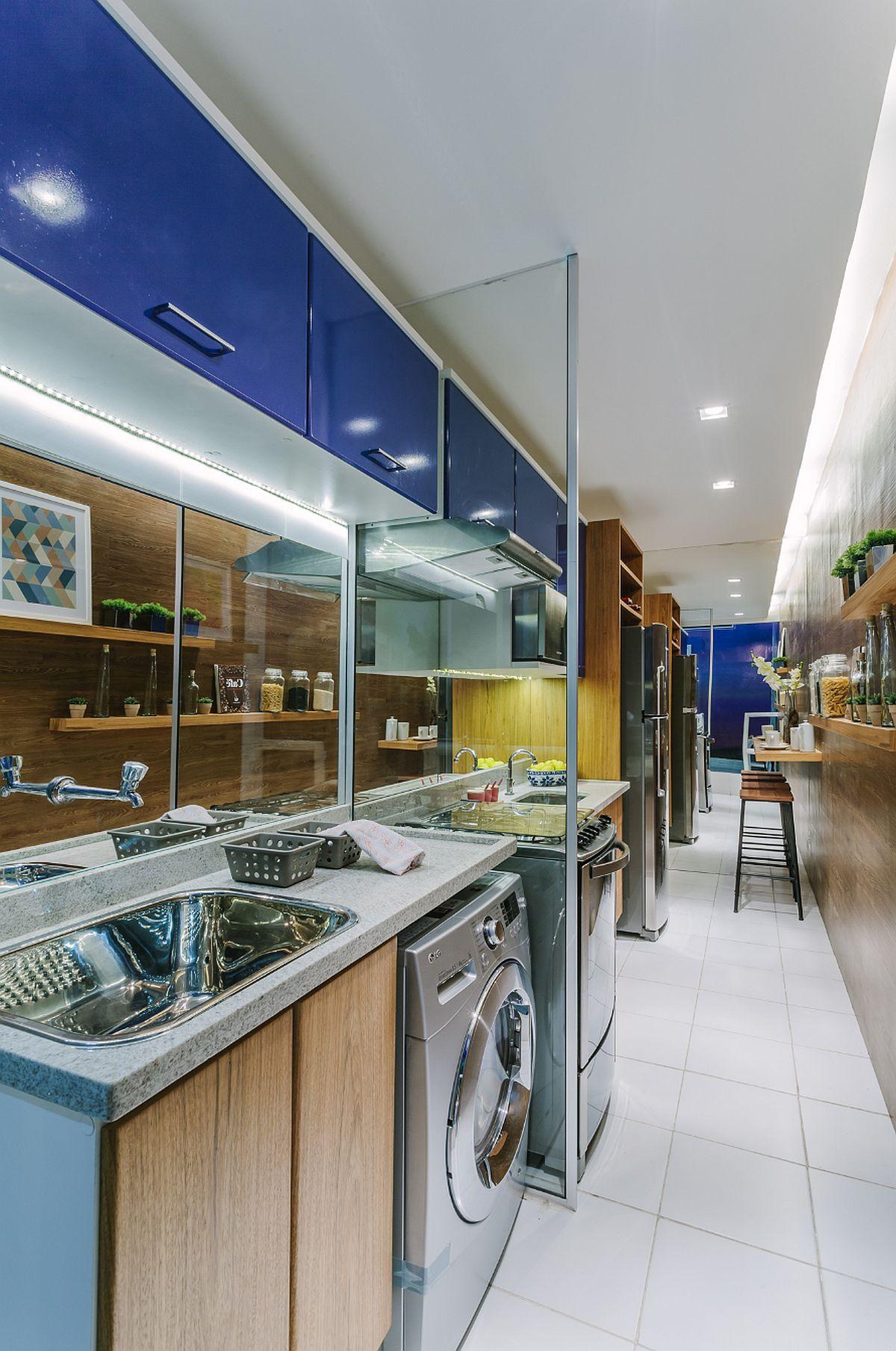 Efectul oglinzilor se simte cel mai bine în bucătărie, unde pe latura îngustă de la intrarea în bucătărie tot peretele este placat. Astfel, spațiul pare și mai lung decât în realitate. Pe lângă locul de masă de la intrarea în bucătărie și zona de gătit pe partea opusă, un paravan separă bucătăria de locul mașini de spălat și al unui lavoar pentru rufe, chiar dacă mobilierul este gândit unitar. Peretele opus moblei a fost placat pentru a fi protejat, dar și din punt de vedere vizual arată bine.