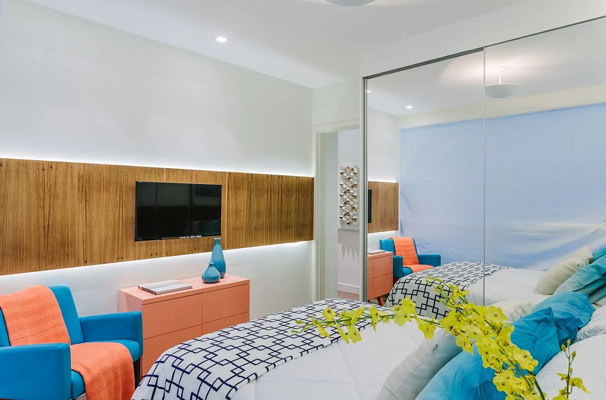 Televizorul este prezent în dormitorul părinților, iar arhitecții s-au gândit să folosească o placare pe orizontală pentru a da senzația de spațiu mai lat. Iluminată din spate cu nezi LED; placare conferă o lumină plăcută pe timpul serii. Un fotoliu și o comodă colorate aduc un plus de exotism camerei care este foarte simplu tratată la nivel de finisaje.