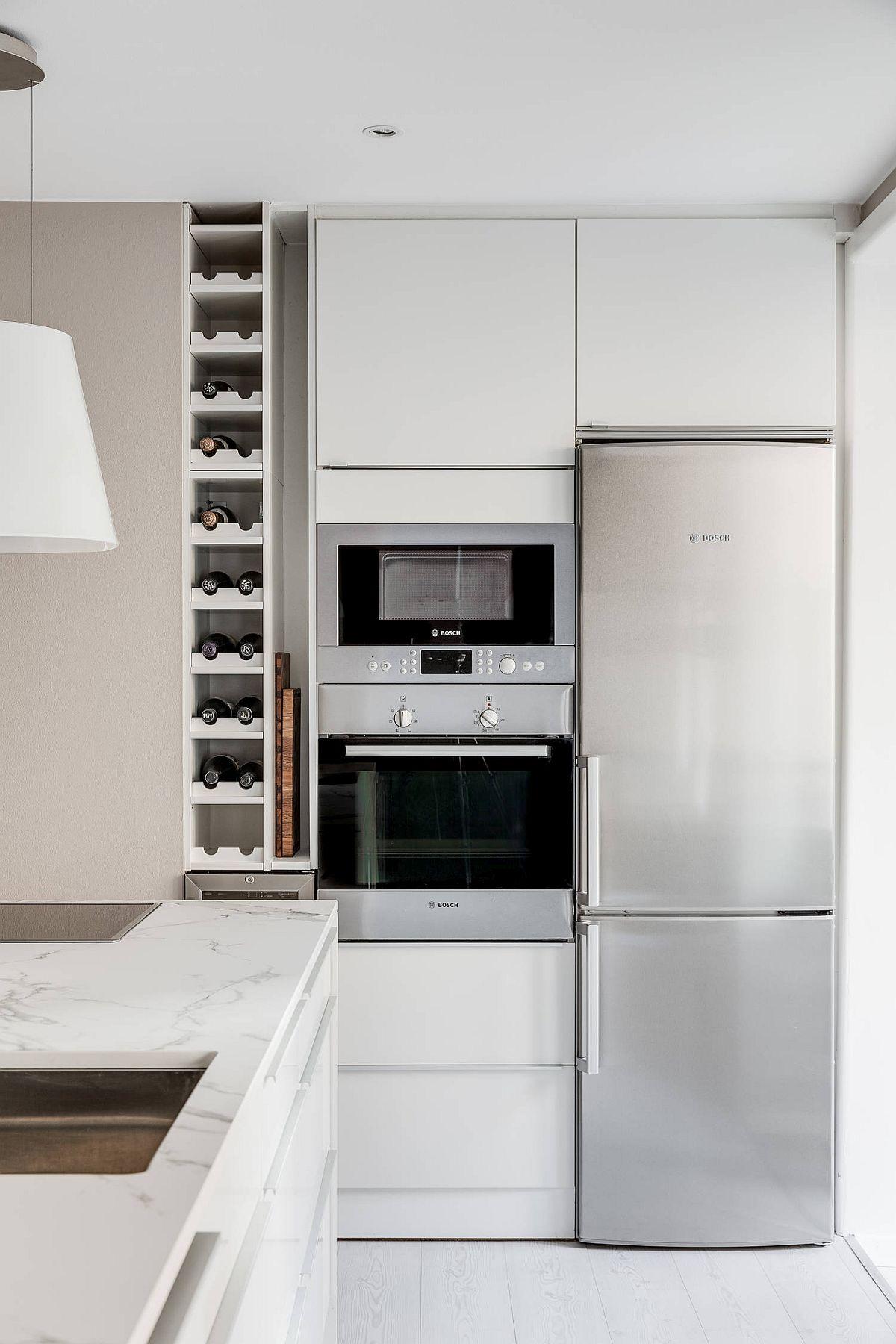Locul pentru electrocasnicele mari este grupat într-o niță a bucătăriei, cu mobilier realizat pe comandă care face tot ansamblu să apară compact.