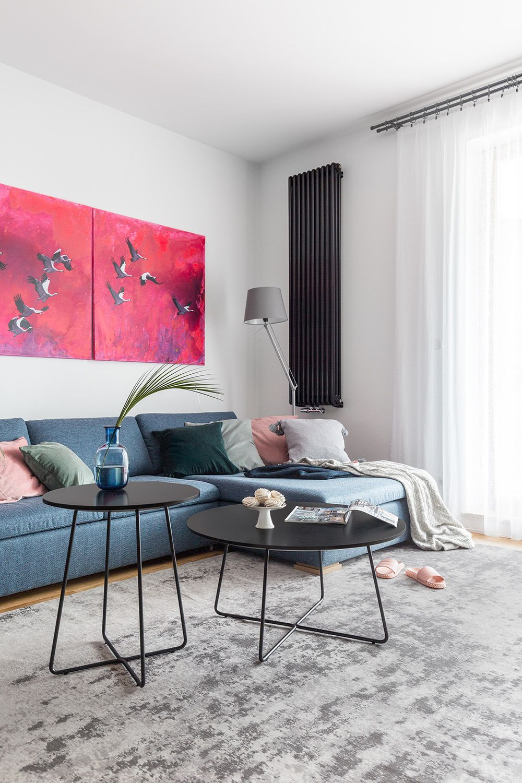 Caloriferele alese sunt negre și sunt dispuse de o parte și de alta a ferestrei generoase din living. Pentru a atenua prezența lor, designerii au ales un tablou contemporan în nuanțe puternice deasupra canapelei. Piesele mici de mobilier sunt zvelte și nu încarcă spațiul, iar covorul are o textură plăcută și o nunață neutră, un gri ce face trecerea dintre pereții albi și cel negru din camera de zi.