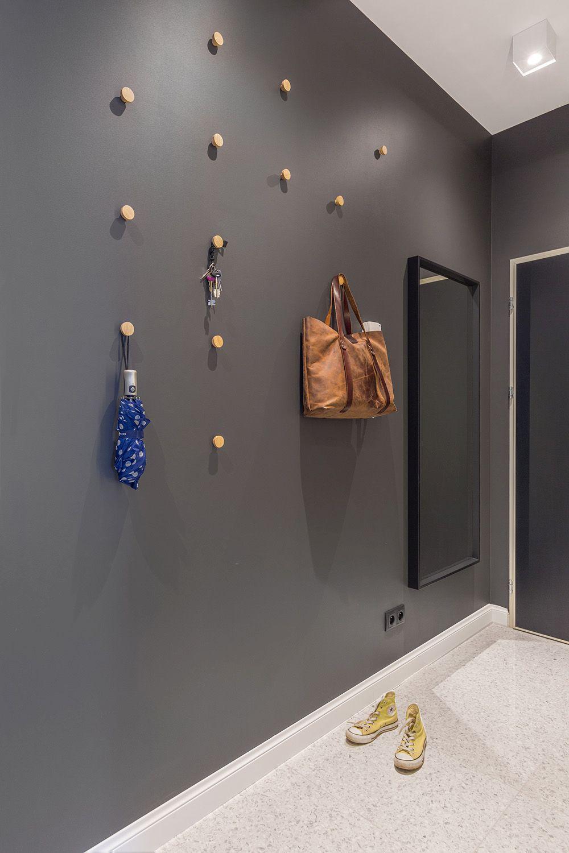 Pentru ca lucrurile des folosite să fie ușor depozitate la intrarea în locuință, designerii au propus ca peretele opus dulapurilor să aibă zonă de cuier. Dar modul cum sunt puse suporturile arată bine și cu și fără obiecte agățate de ele.