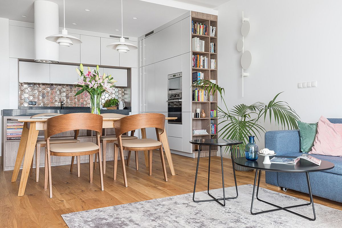 Toate spațiile bucătăriei sunt închise, dar legătura cu livingul este realizată printr-un corp de bibliotecă lung și îngust. Astfel, mobila de bucătărie nu pare că se termină brusc în ansamblul camerei de zi.