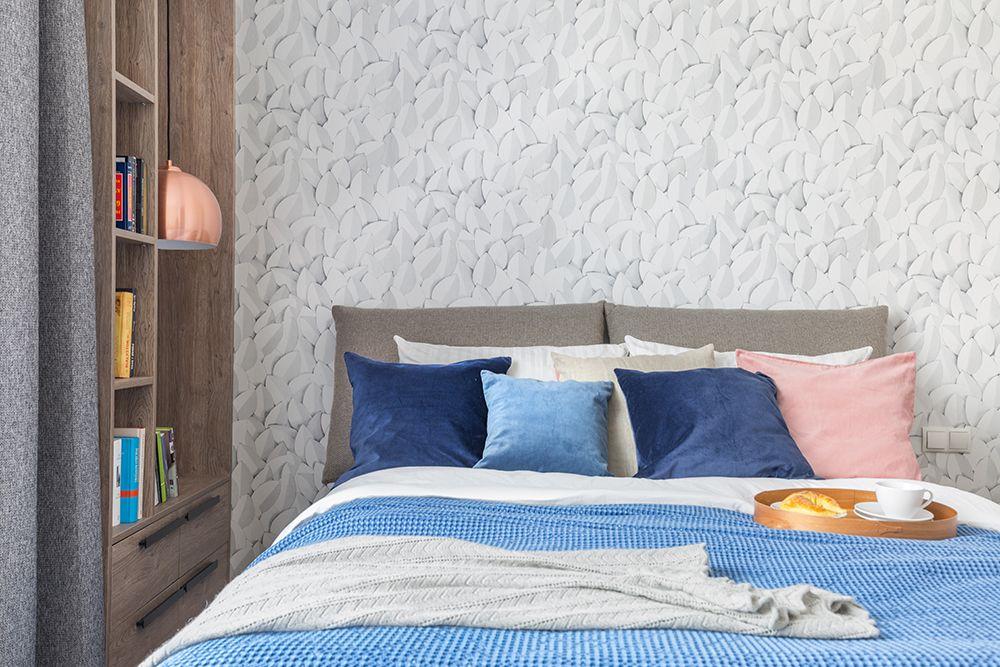 Zona tăbliei de pat a fost personalizată cu un tapet imprimat cu un model 3D. În locul noptierelor, spațiu îngust a fost exploatat cu o bibliotecă configurată în lateralul ferestrei și aproape de pat.