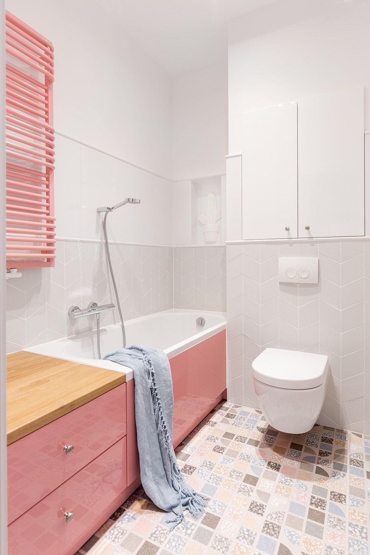 A doua baie are suprafețele mari finisate cu plăci ceramice în nuanțe deschise și mult alb care contrabalansează rozul prezent aici la nivelul finisajelor mobilei, măștii de cadă și caloriferului.