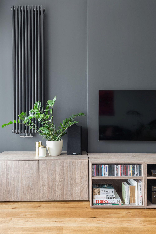 Pentru a atenua contrastele cu ecranul tv și caloriferul, dar ;i și pentru a crea senzaía de adâncime, peretele din living este vopsit într-o nuanță închisă. Contrastul cu mobila însă conferă un aer plăcut, punând în valoare texturile similare lemnului. Comoda joasă are și spații de depozitare închise pentru mai multă ordine în zona de zi. De asemenea, spațiul este perceput ca aerisit, având în vedere dispoziția mobilierului.