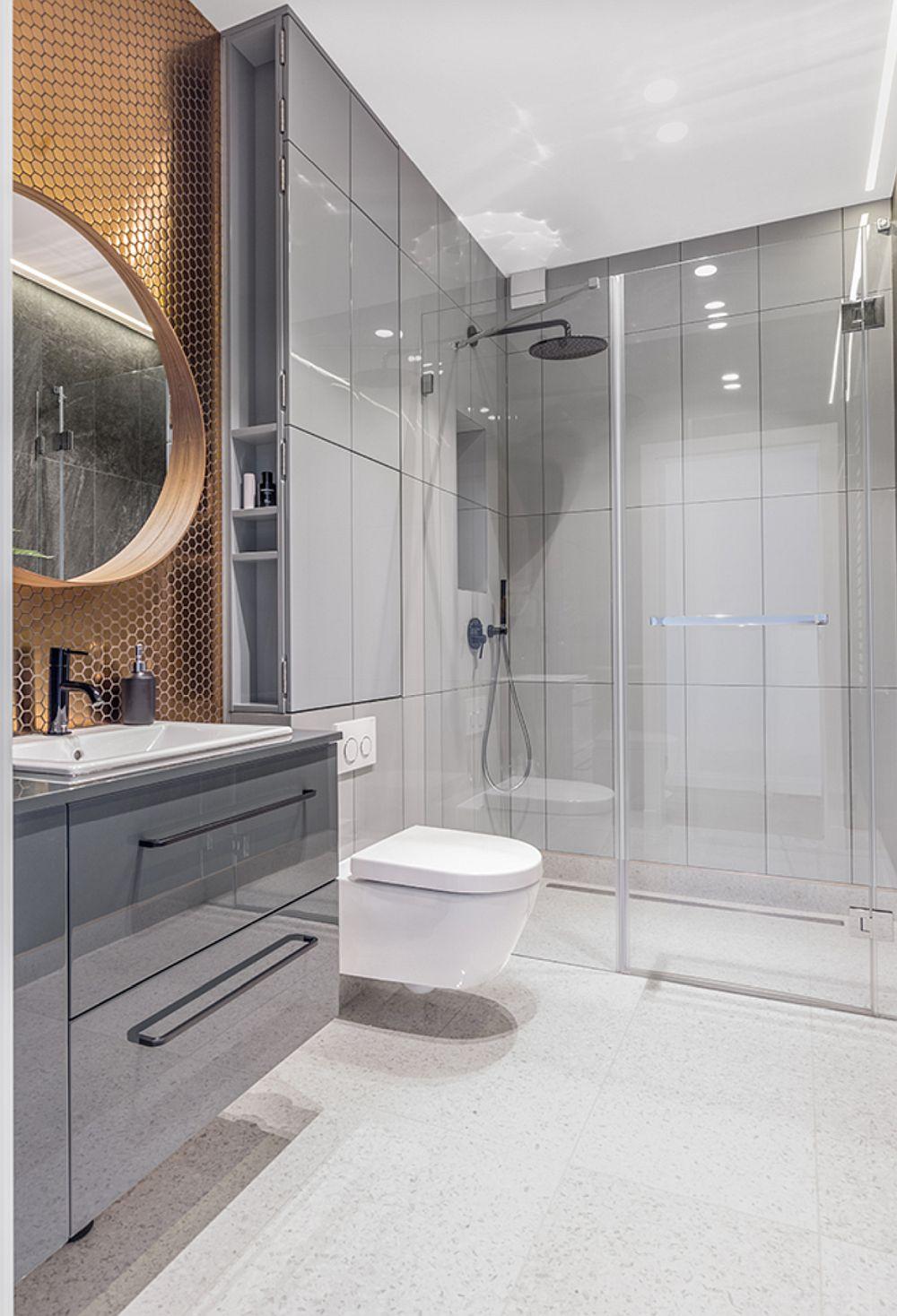 Baia principală este funcțional și minimalist tratată cu duș separat printr-un panou de sticlă și cu rigolă în pardoseală. Plăcile alese pentru pardoseală, deschise ca nuanță dau impresia de spațiu mai mare.