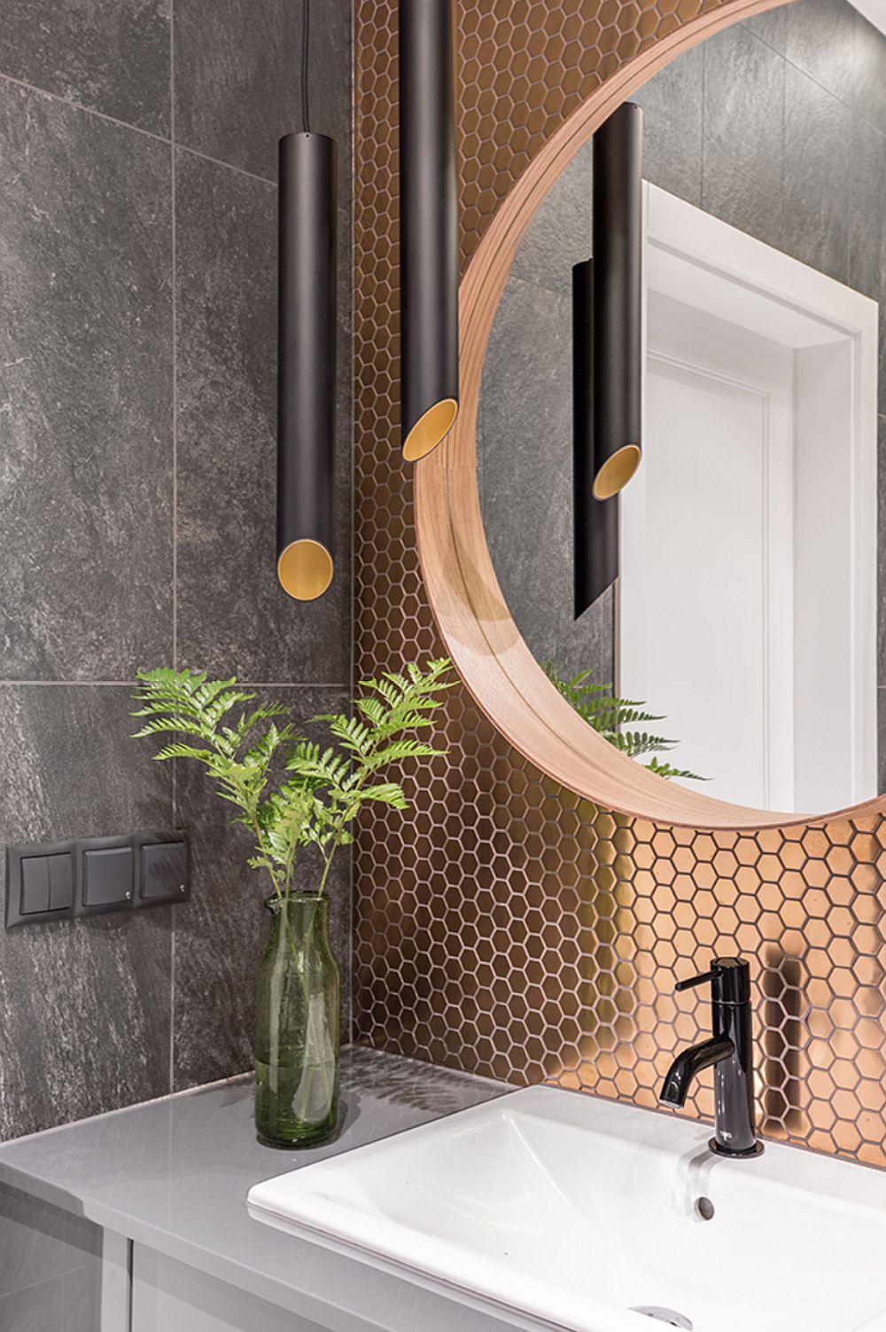 Pentru ca baia să aibă o notă personalizată, dar totodată și elegantă, peretele din zona de lavoar este îmbrăcată cu mozaic cu efect metalic.