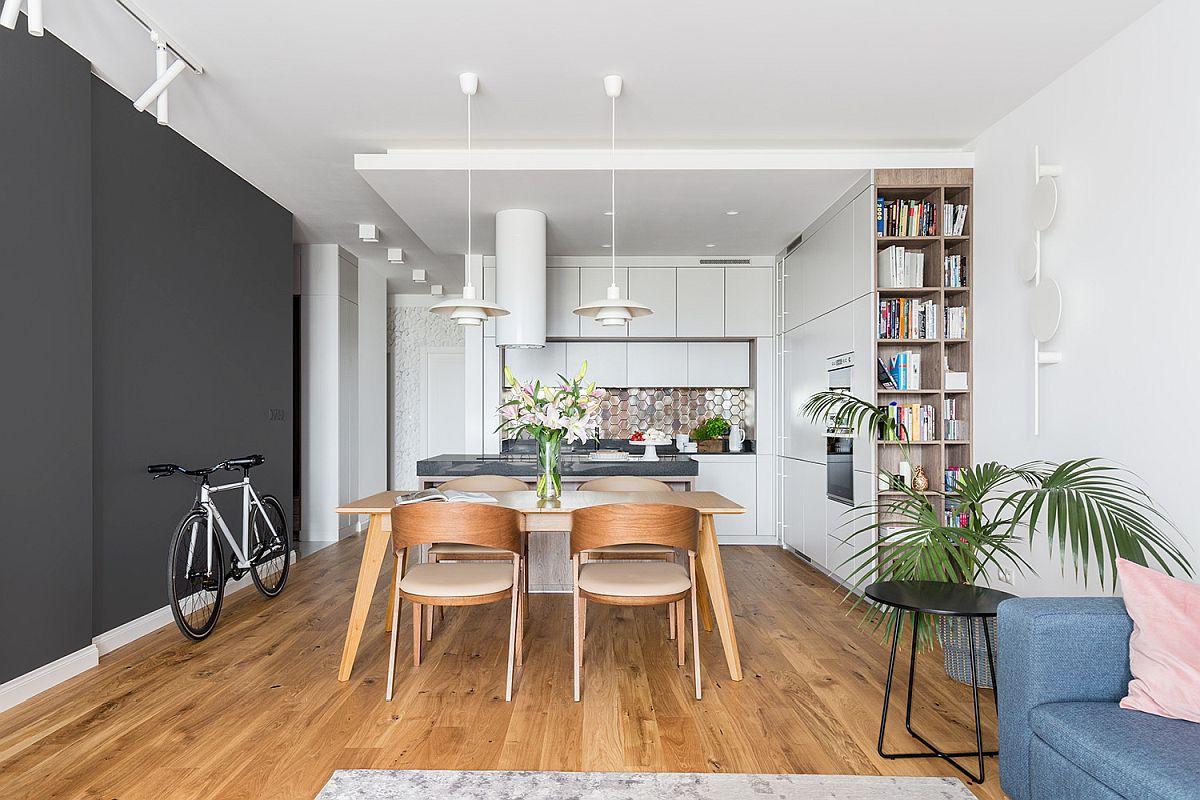 Cel mai mare spațiu din locuință este dedicat zonei de zi, unde sunt grupate bucătăria, sufrageria și livingul. Spațiul mai mult lung și îngust a fost tratat scenografic, respectiv unul dintre pereți (cu locul de tv) este vopsit într-o nuanță închisă, care dă impresia de adâncime. În rest, atât mobila, cât și pereții sunt albi pentru o mai bună luminozitate.