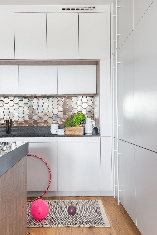 Pentru un aspect ordonat mobila de bucătărie a fost configurată fără mânere și ocupă tot spațiul pe verticală. Pentru combina frigorifică însă, sistemele push nu sunt eficiente, așa că designerii au prevăzut mânere subțiri montate în șir pentru a da un aspect coerent. Două mînere pentru frigider și congelator ar fi arătat stinghere, dar așa totul este mai armonios vizual.