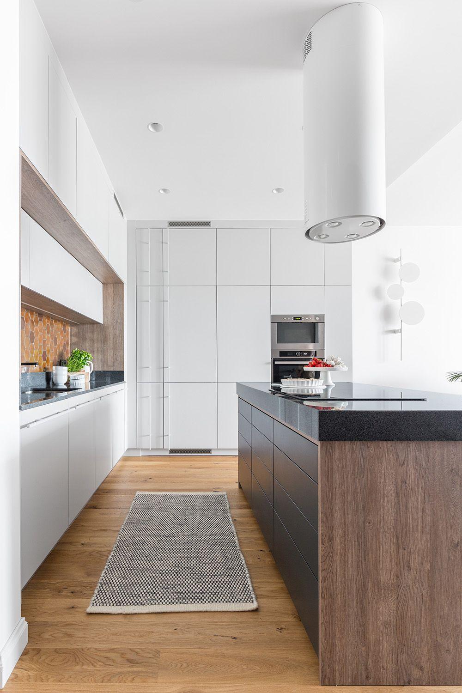 Din holul de la intrarea primul spațiu care se vede este cel al bucătăriei. Pentru ca spațiul de depozitare în bucătărie să fie mai generos, designerii au prevăzut aici o masă insulă în care este montată plita electrică. Sertare numeroase asigură un spațiu de depozitare mare, ușor manevrabil și vizibil într-un spațiu îngust.