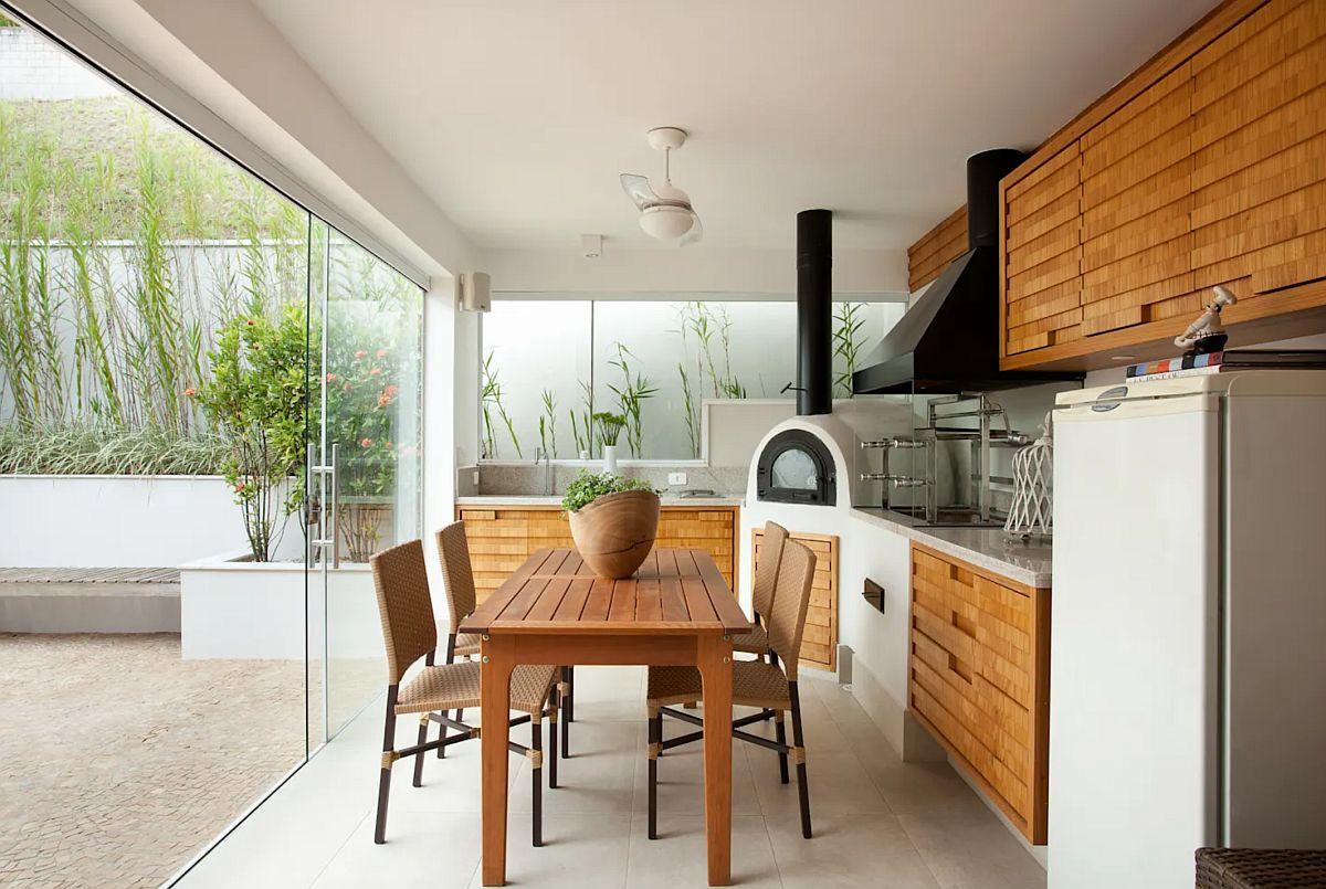 Mobila de bucătărie este realizată din structuri fixe, zidite, în acord cu gardul și amenajarea peisagistică de afară pentru coordonare vizuală, dar și pentru ca acst mobilier să fie rezistent în timp. Fronturile sunt realizate din lemn exotic. Oricât de mult s-ar prelungi perioada de ședere în bucătăria de vară, separarea cu panouri din sticlă nu poate asigura confort termic pe timp de iarnă, ca atare mobilierul fix e bine să fie unul rezistent, mai ales la umezeală.