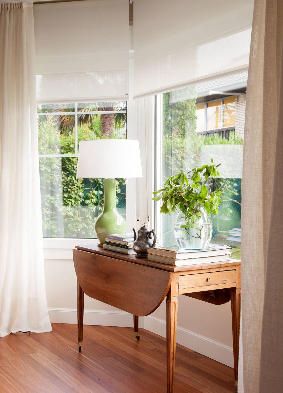 Când vrei ca un spațiu mic să se simtă mai aerisit, zona ferestrelor merită tratată cât mai lejer, cu suprafața de geam cât mai liberă. Aici , combinația de rolete simple albe cu draperii deschise în lateral rezolvă atât problema intimității, umbririi, cât și pe cea estetică de coordonare cu linia clasică urmărită.