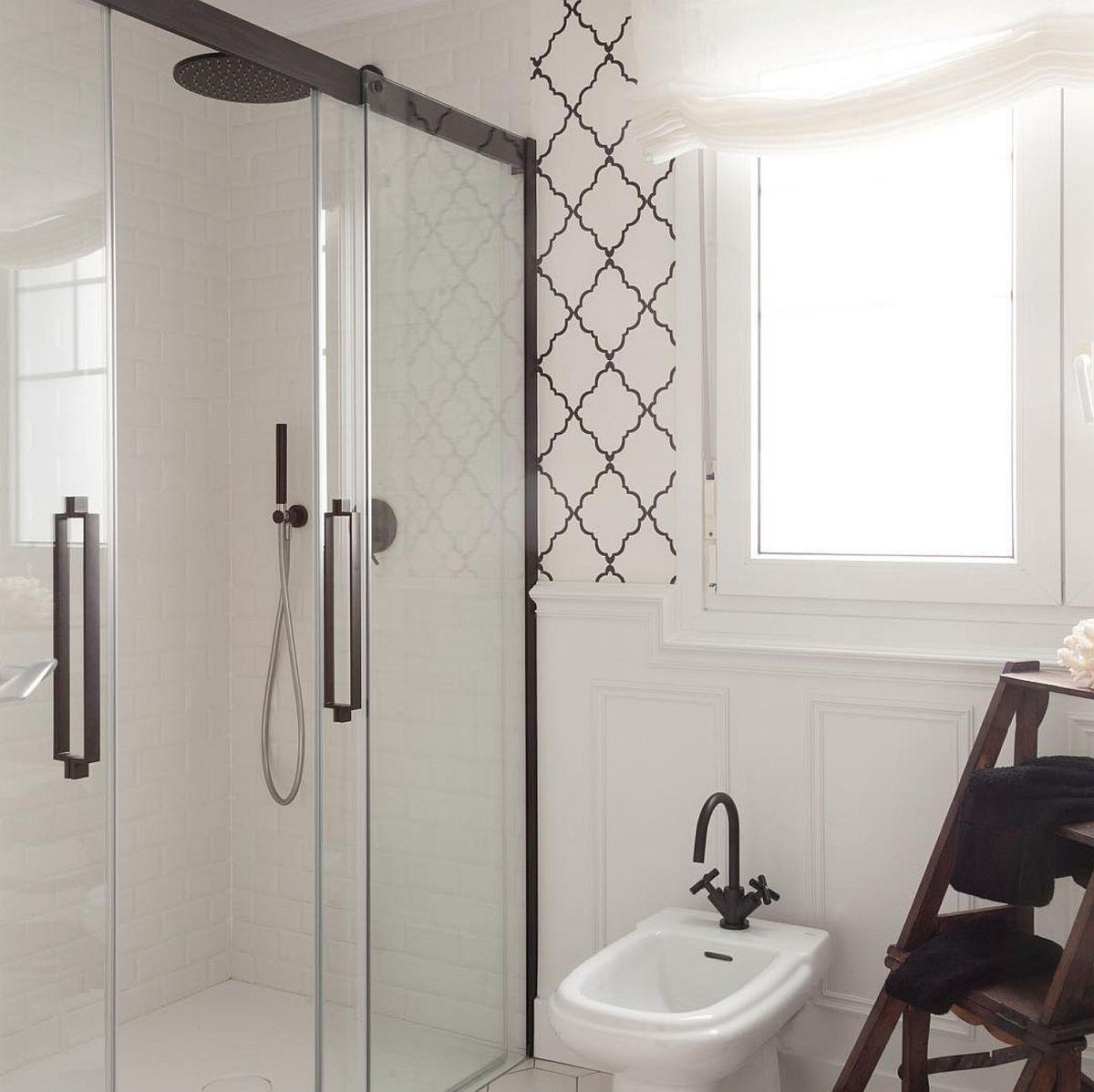 Baia a fost complet renovată, deci inclusiv zona de duș unde panourile din sticlă sunt încadrate de profile negre. Tapetul este folosit și aici, dar nu în zona sensibilă, ci în jurul ferestrei.