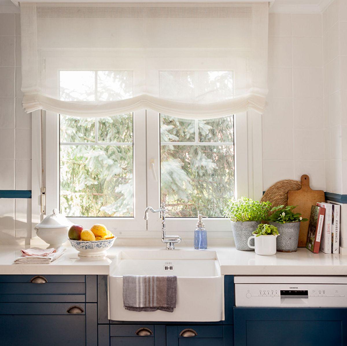 Evident că nu putea lipsi dintr-o bucătărie cu tușe englezești chiuveta din fața ferestrei. Dar nu e vorba numai de chiuvetă, ci și de modul de decorare al întregului spațiu, de la storul alb care încadrează fereastra cu șprosuri la designul mobilierului de bucătărie. Mult alb, care oferă mai multă luminozitate, dar și senzația de spațiu amplu și ordonat, curat.