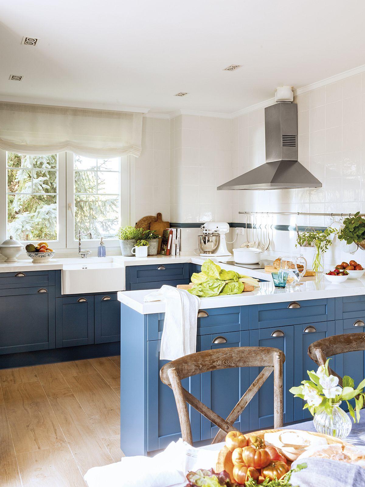 Bucătăria este excelent organizată în două zone: prima alocată gătitului, a doua destinată locului de luat masa. În zona de gătit, designerul a prevăzut o amplasare în U a mobilierului pentru a mări suprafața blatului, dar și pentru a fi prezente mai multe spații de depozitare. Proprietara este fotograf culinar și a visat la o bucătărie albastră cu blat alb, care dă foarte bine în imagini, un contrast excelent cu diversele preparate.