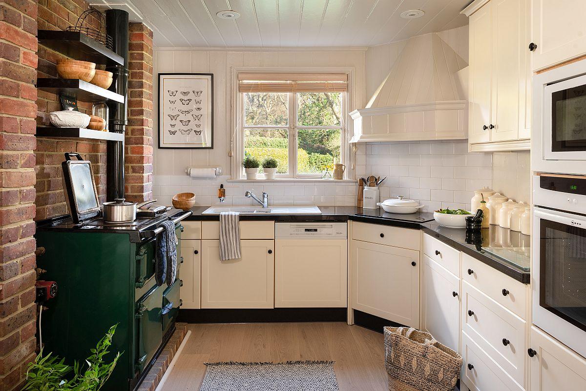 Bucătăria a fost complet remodelată și dotată cu electrocasnice noi. Acestea au fost alese cu fața albă pentru a fi mai frumos integrate în mobilierul deschis la culoare. Blatul negru nu lasă să se vadă plita actuală montată pe colț, chiar dacă hota decorativă iese în evidență. Pentru un aspect elegant și aerisit zona de fereastră nu are corpuri suspendate sau rafturi tocmai pentru a accentua peisajul care se vede prin geamuri.