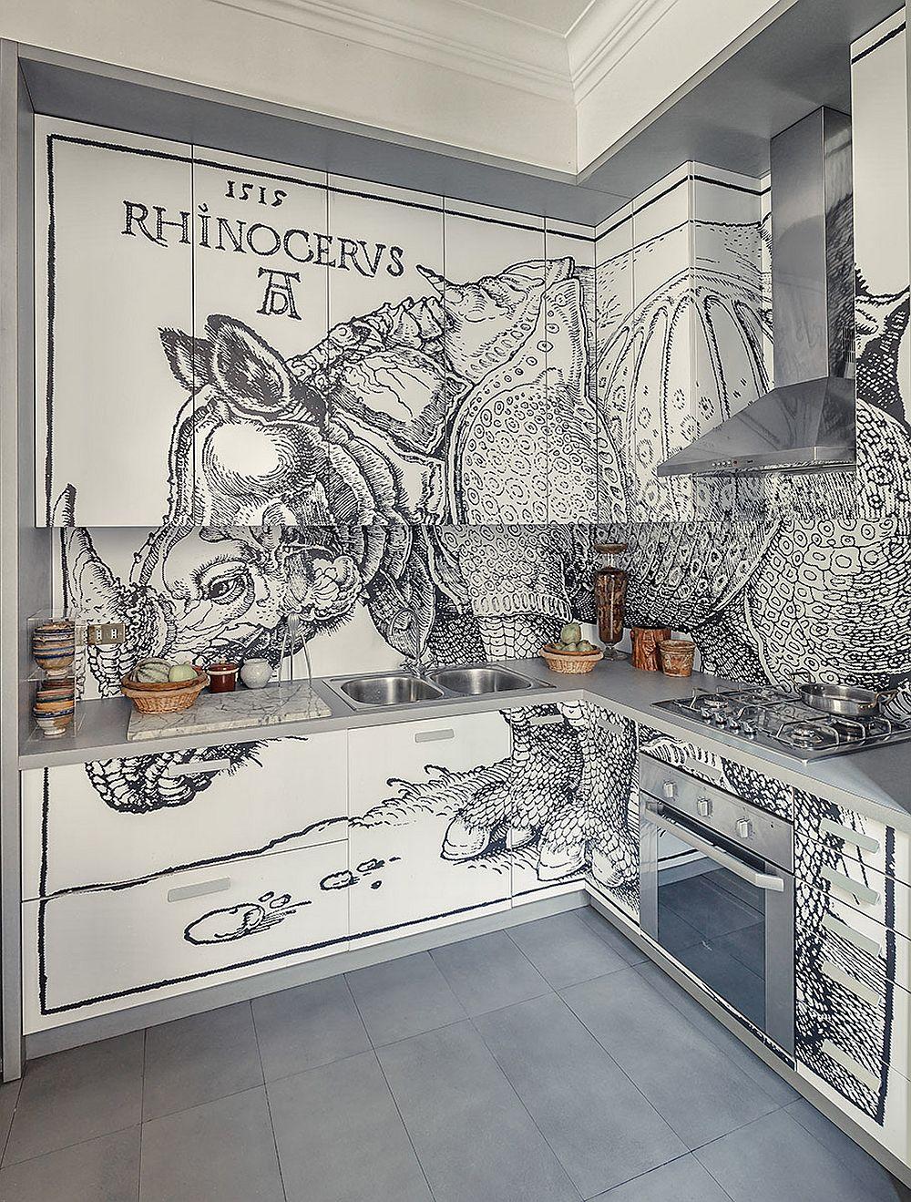 """Te-ai fi așteptat la o astfel de bucătărie? Cu siguranță nu. Dar proprietarul acestei case a dorit ca fiecare încăpere să exprime ceva care să-l fascineze. Pe fețele mobilierului de bucătărie este imprimată o reproducere după celebrare lucrare """"Rhino"""" a lui Albrecht Dürer (1515), una dintre cele mai influente și copiate lucrări în Europa timp de trei secole. Reprezentarea rinocerului este una imaginată, după descrieri, artistul renascentist german, neavând ocazia să vadă în realitate vreun exemplar. Deși realizată după descrieri în 1515, lucrarea realizată în lemn este surprinzător de actuală și azi, ca tehnică de reprezentare."""