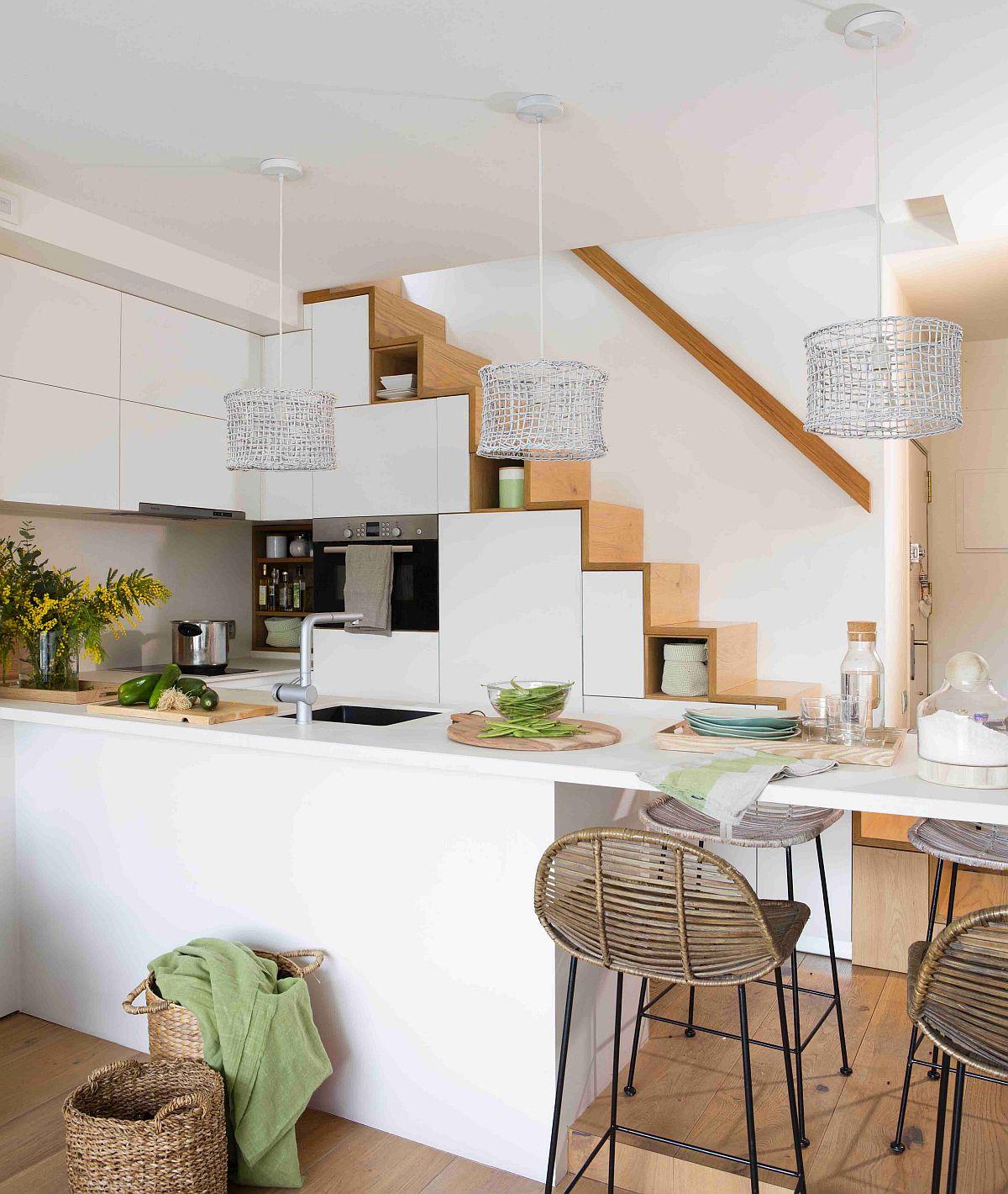 Bucătărie este ingenios amenajată în vecinătatea scării. Mobila realizată pe comandă a fost gândită să preia și rolul de scară interioară, iar sub ea să fie configurate spații de depozitare.