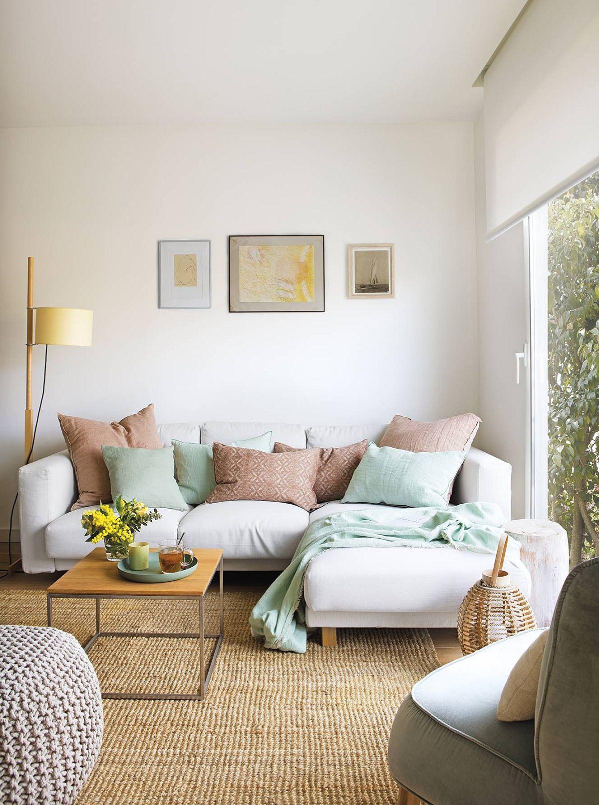 Cu perne decorative și cîteva tablouri sunt asigurate petele de culoare în zona de canapea, unde suprafețele mari sunt o combinație de alb și texturi naturale.