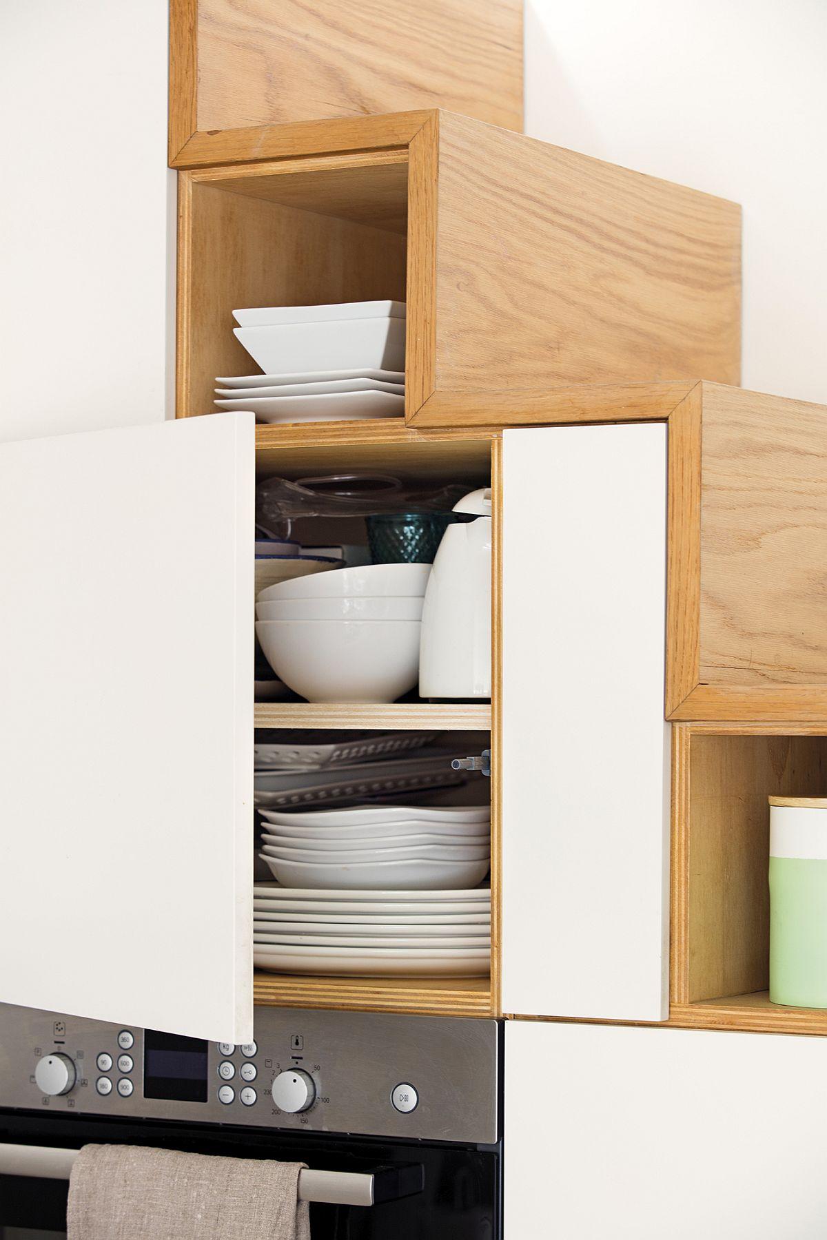 Cu mobiă făută pe comandă, fiecare zonă de sub scară a devenit utilă. Frigiderul este încorporat și el în mobilier, imediat lângă cuptor. Pentru că spațiul este îngust, designerul a prevăzut o mobilă fără mânere, ușile fiind dotate cu sisteme push.