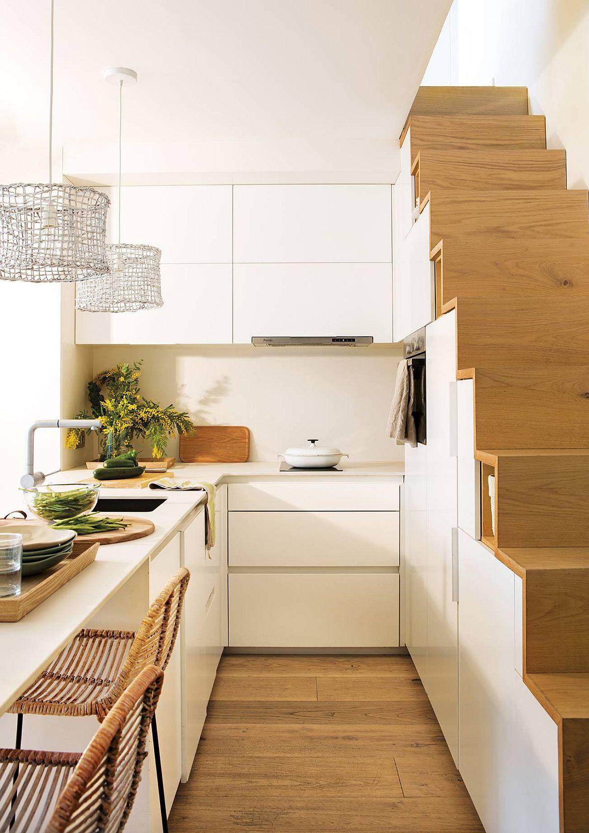 Chiar dacă spațiul este mic și îngust, bucătăria este excelent organizată. Pentru a exploata fiecare centimetru pătrat, designerul a prevăzut o plită cu două ochiuri în loc de una clasică, iar cuptorul a fost poziționat la înălțime, pentur ca sub blat să existe sertare pentru depozitare.