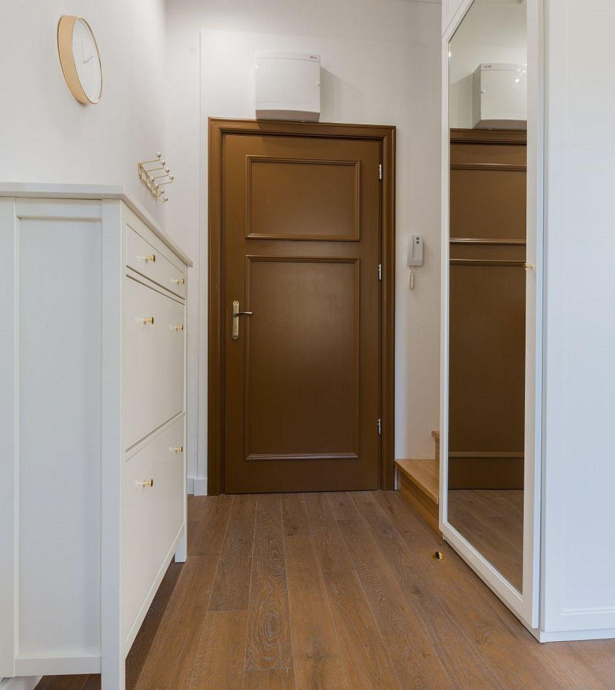 Chiar dacă e o locuință mică, holul de acces este generos și ferit privirii din cameră. De aici se deschide și scara interioară către dormitor.