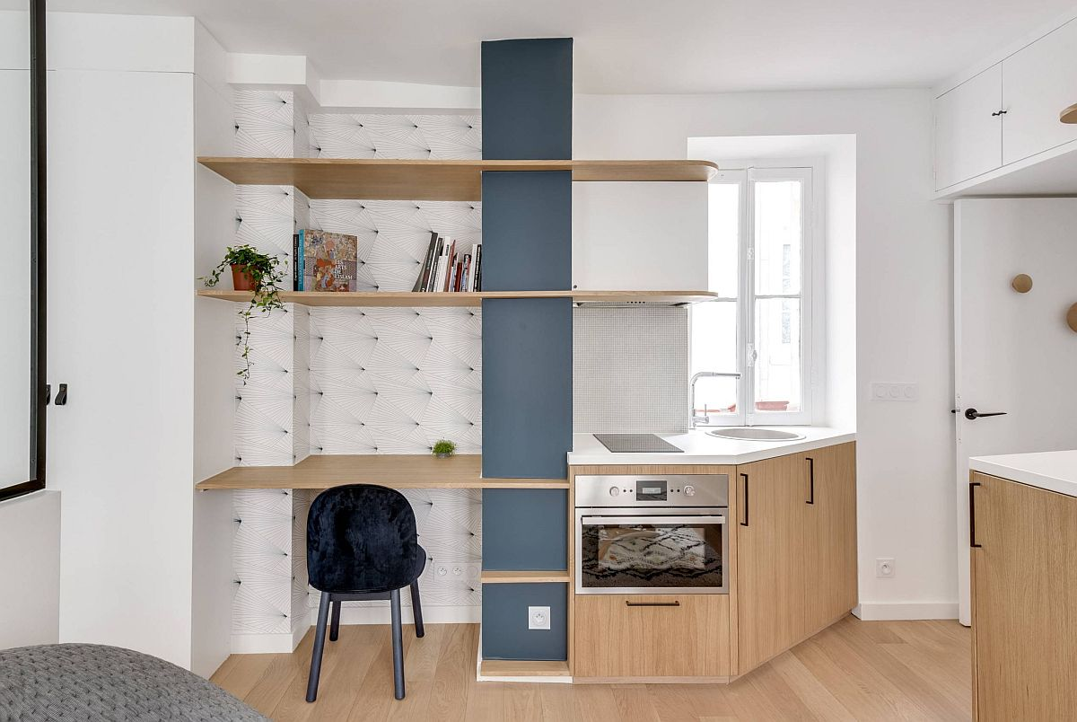 După renovare locul bucătăriei a fost păstrat, dar reconfigurat. Pentru a nu bloca accesul în cameră, mobila a fost gândită în unghi, iar în partea superioară doar cu rafturi pentru a nu bloca lumina ferestrei din zonă. Frigiderul a fost poziționat în ansamblul de mobilă din zona de tv (aici se vede colț dreapta). Compromisurile sunt evidente cu spațiu mic între plită și chiuvetă și prezența unui frigider mic în locul unei combine frigorifice.