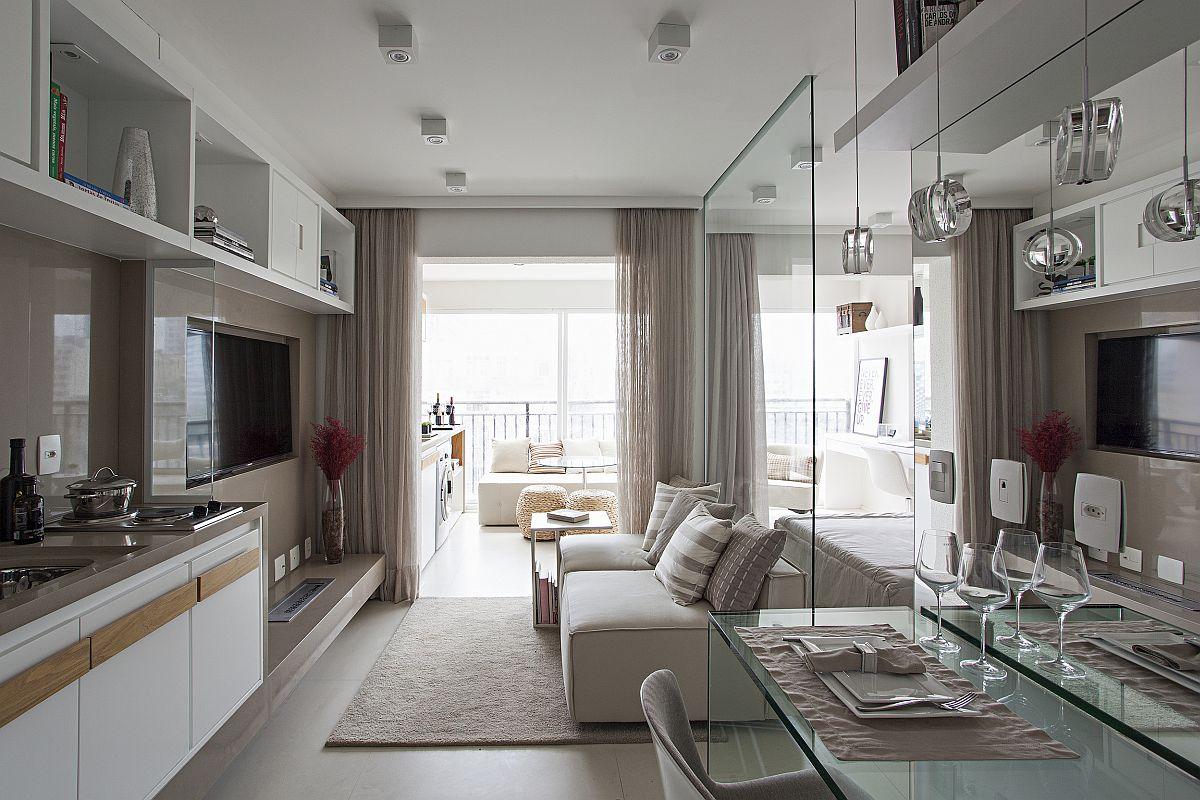 De la intrarea în locuință se vede zona de zi, cu locul de tv și canapea și deschiderea către loggia acum integrată în ambient.
