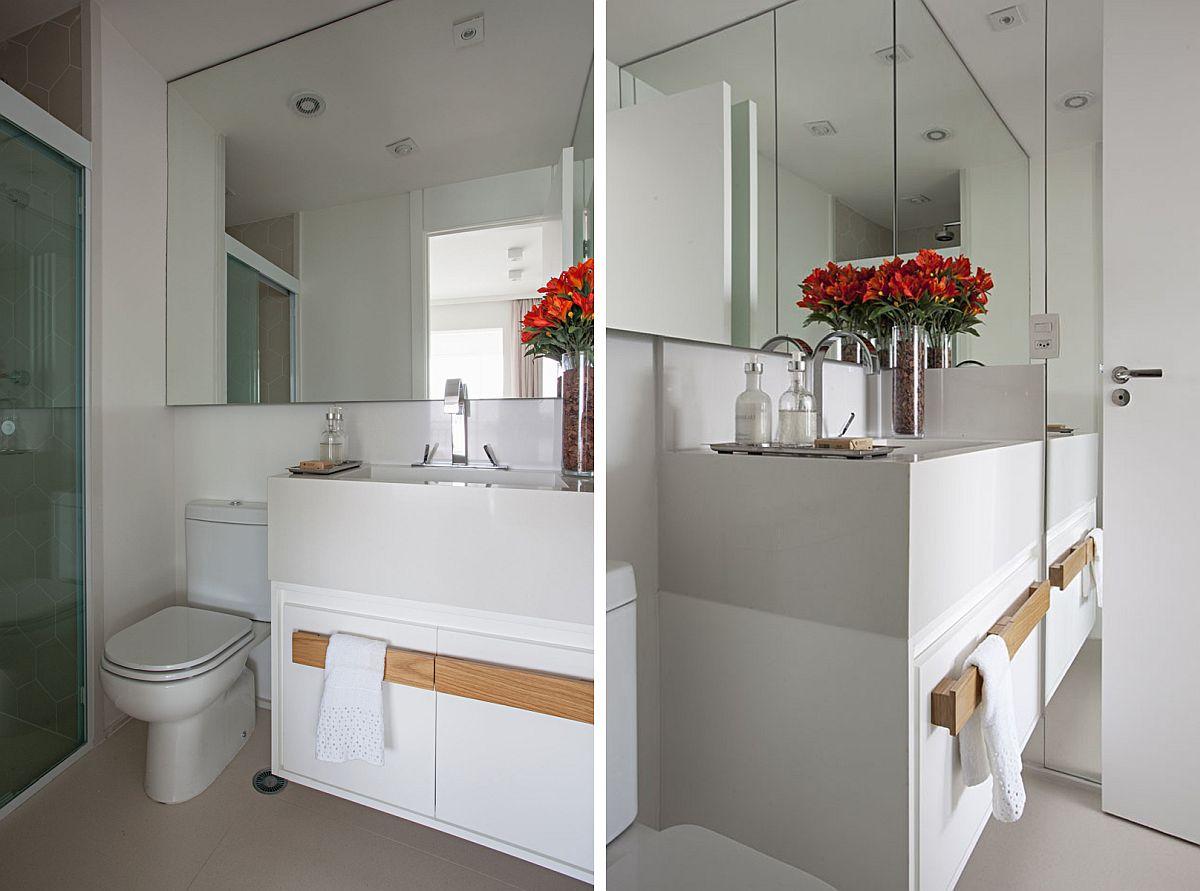 Pentru că nu beneficiază de lumină naturală, baia beneficiază de o oglindă supradimenionată.