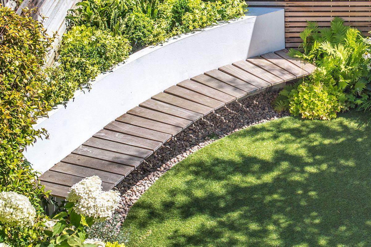 Locul de ședere a fost conceput ca o jardinieră fixă de care sunt prinse în console lamele de lemn exotic.