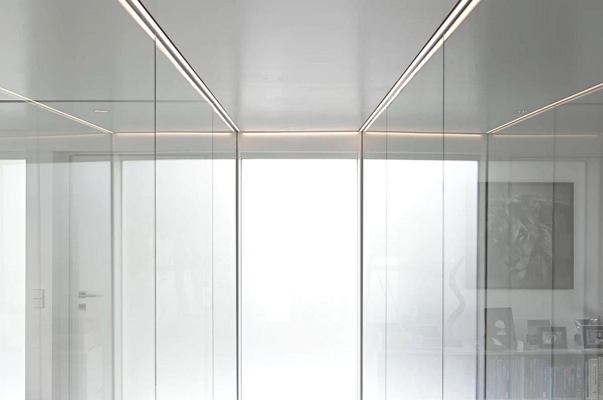 Detaliu de execuția de la nivelul plafonului din zona scării de acces către demisol demarcată de panouri din sticlă.