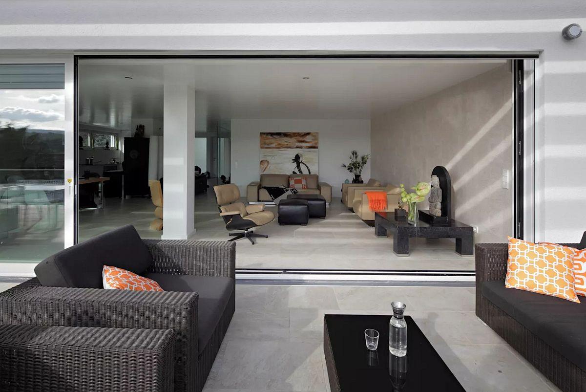 Suprafața mare vitrată asigură lumină naturală din plin la interior. De asemenea, zonele de zi - sufrageria și livingul sunt orientate către terasa generoasă a parterului, situat deasupra nivelului grădinii.